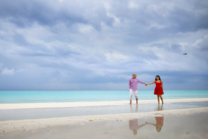 playa del carmen beach portraits, couple walking, rain blue ocean skies red dress reflection