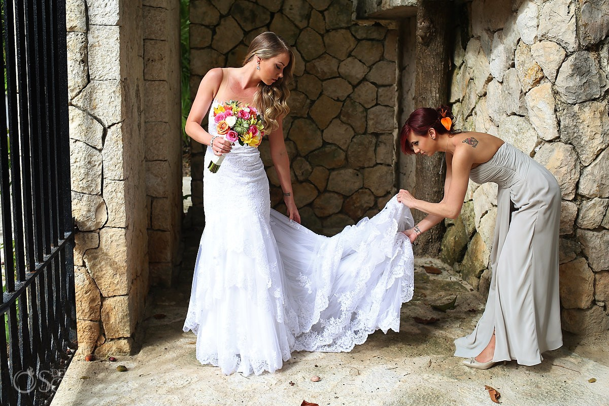 Bridesmaid helping bride Essense of Australia wedding dress, Xcaret Park, Playa del Carmen, Mexico