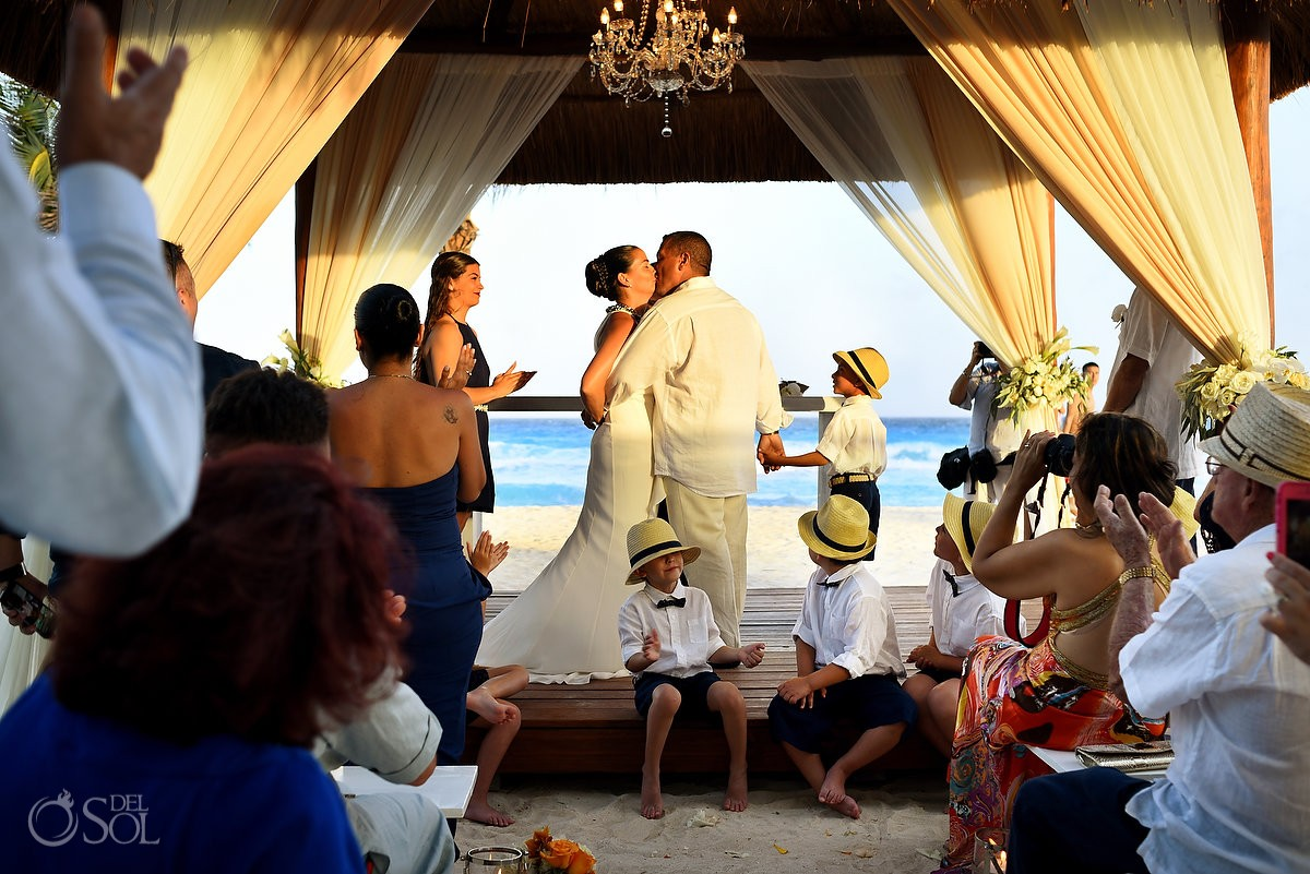 destination wedding photo of first kiss by bride and groom in front of the ocean