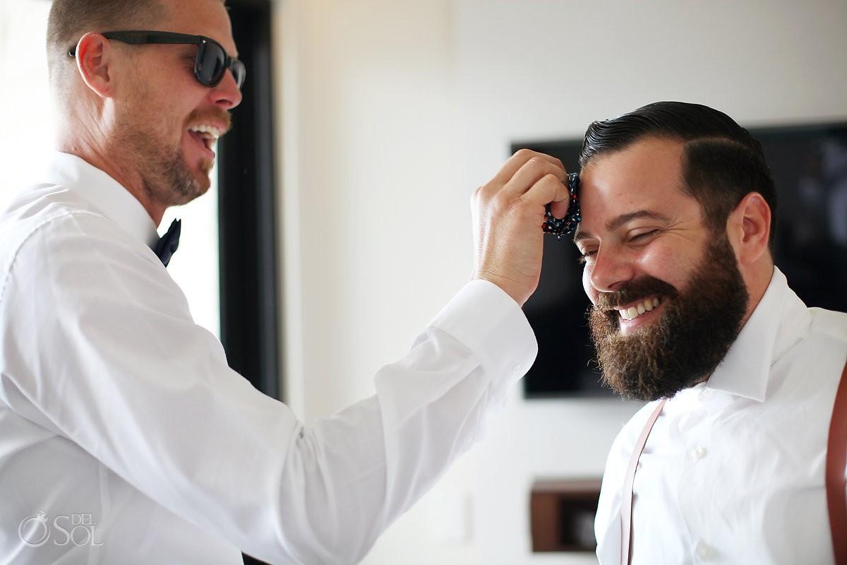 funny wedding picture groomsman wipes groom's sweat, getting ready destination Wedding Grand Hyatt Playa del Carmen Mexico