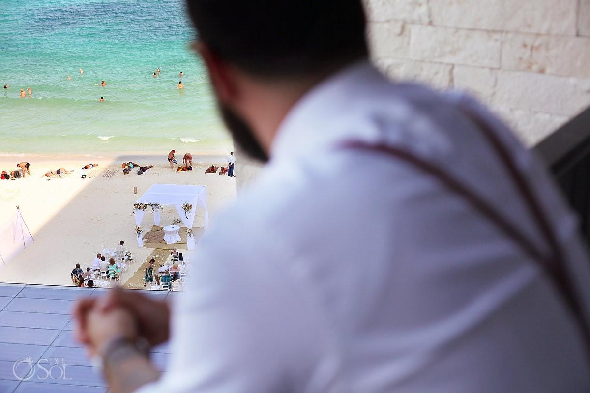 groom looks out of balcony beach Wedding setup Grand Hyatt Playa del Carmen Mexico