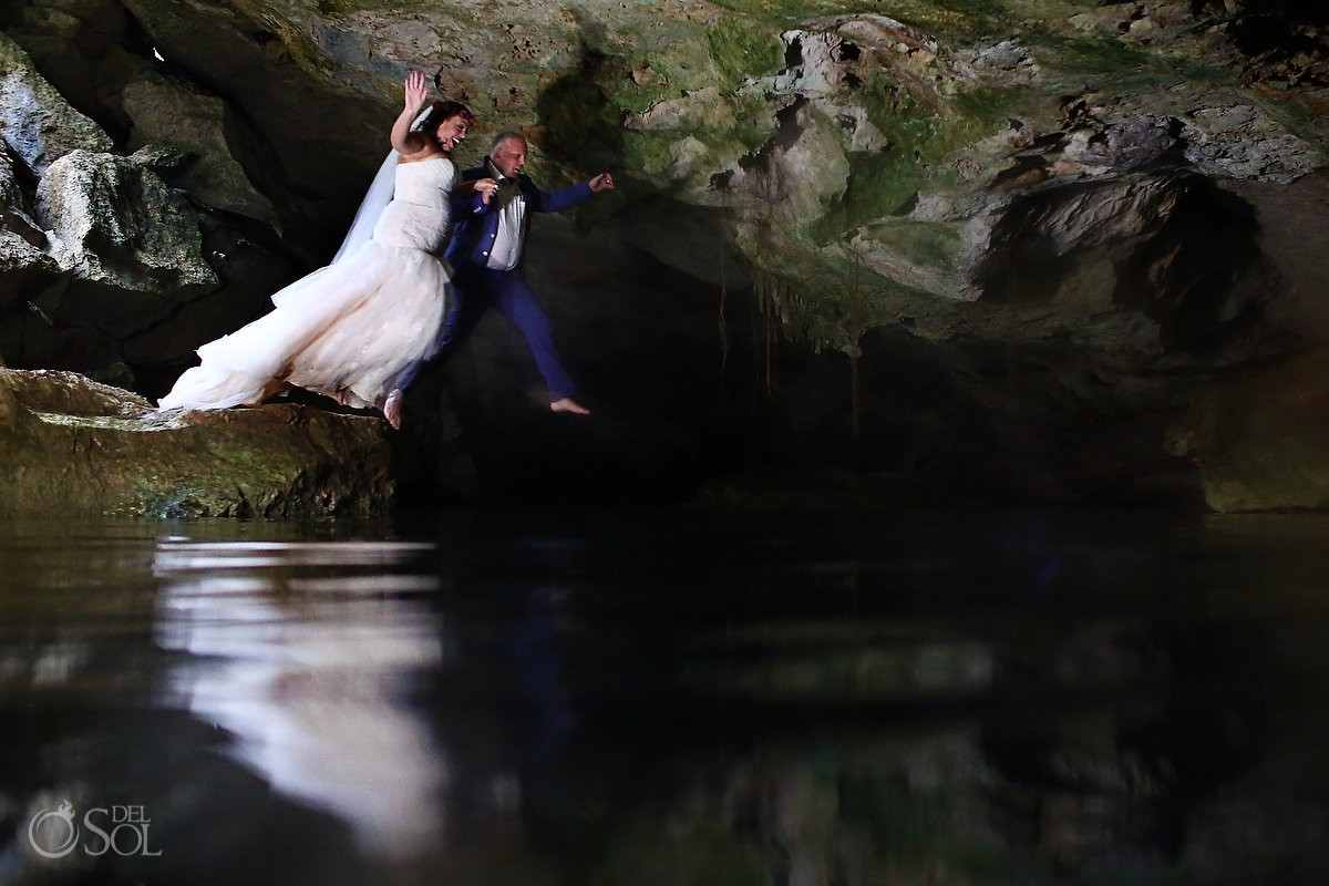 funny wedding photo bride and groom jumping into water cenote trash the dress
