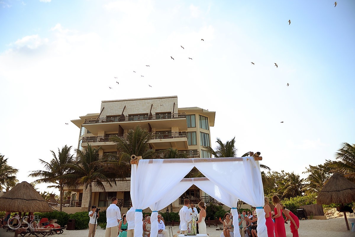 birds flying above beach wedding ceremony Dreams Riviera Cancun