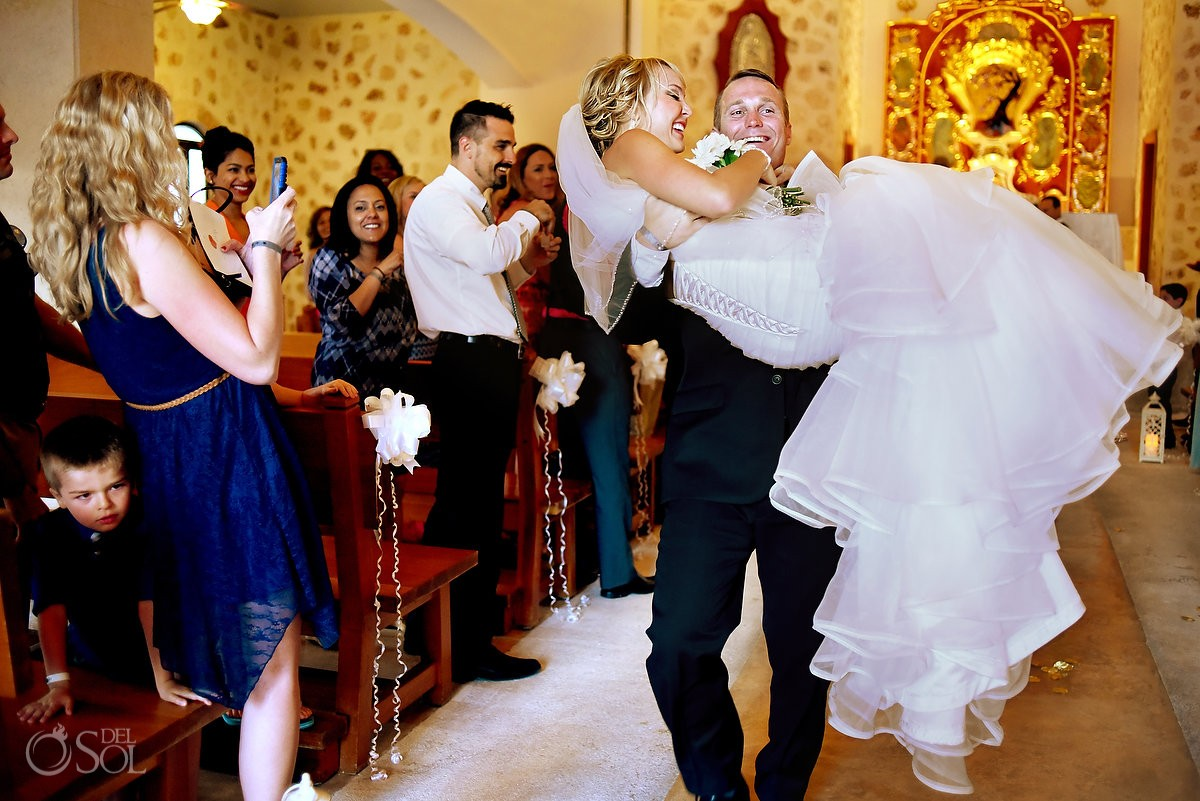 groom carries bride out of churchwedding Iberostar Paraiso Lindo chapel our lady of paradise, Riviera Maya, Mexico