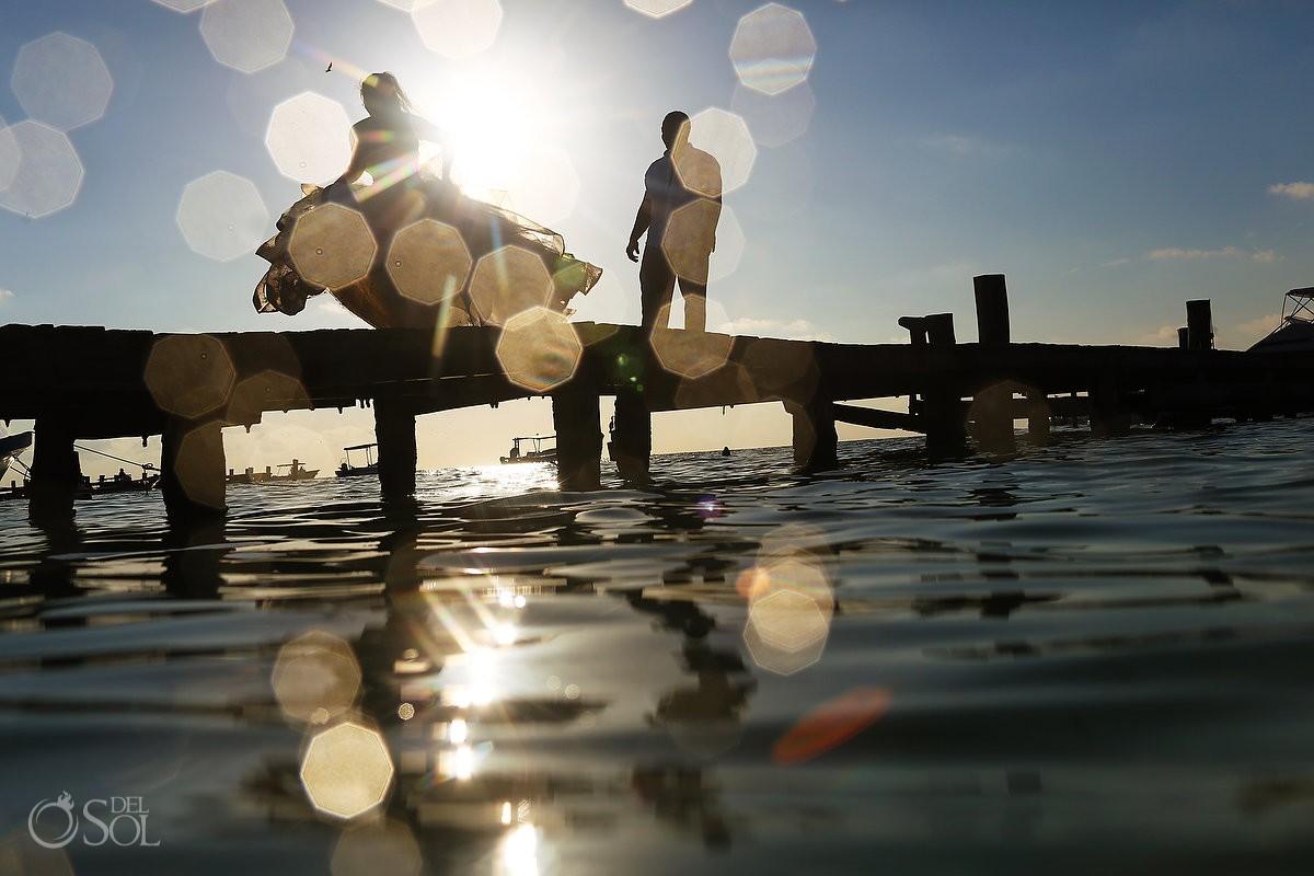 Artistic beach trash the dress silhouette bride happy dancing Sunrise wedding portrait Puerto Morellos pier, Mexico
