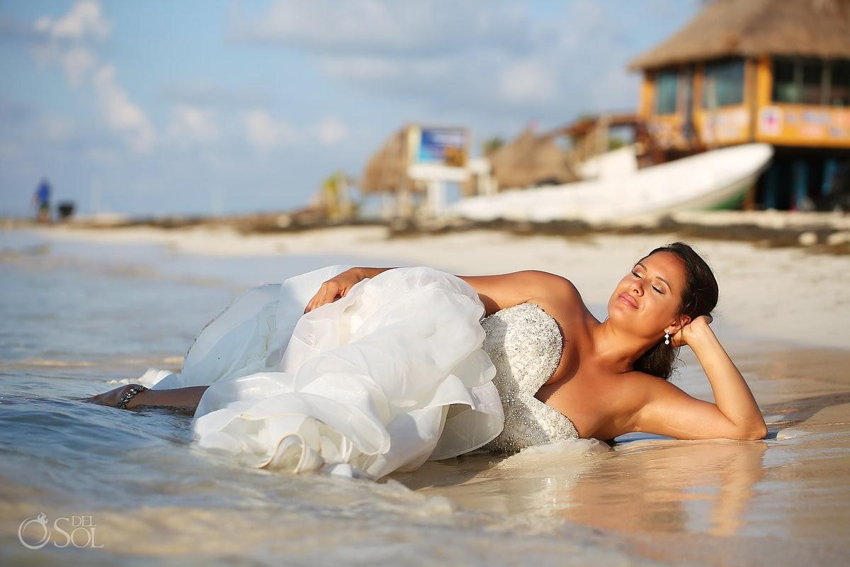mermaid bride wearing Eddy K dress lying water ocean Sunrise wedding portraitPuerto Morelo, Mexico