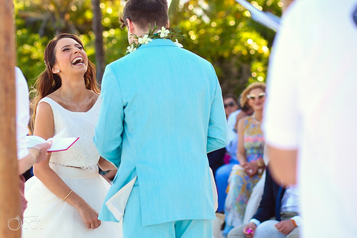 groom wears turquoise suit with bride laughing for beach wedding at hotel esencia