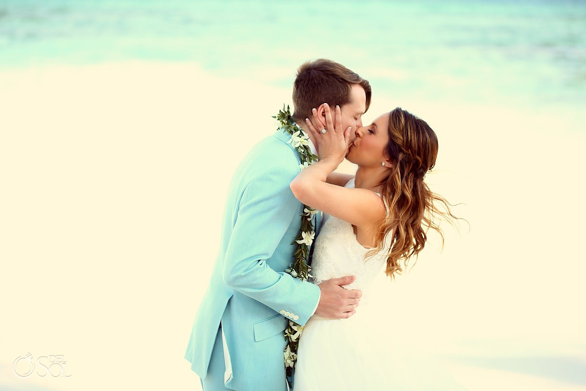 groom wearing turquoise suit kissing bride for a beach destination wedding