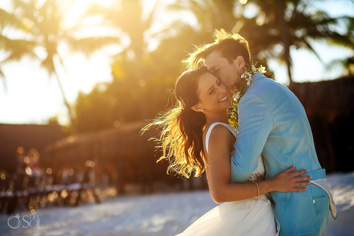 groom wearing turquoise suit kisses bride at hotel esencia beach