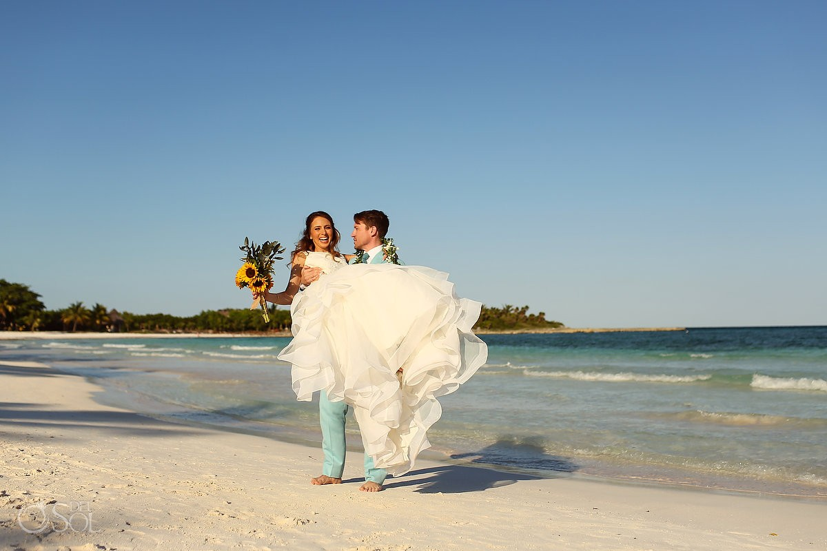 groom with Maile Lei taken from Hawaiian tradition carries destination wedding bride on mexico beaches
