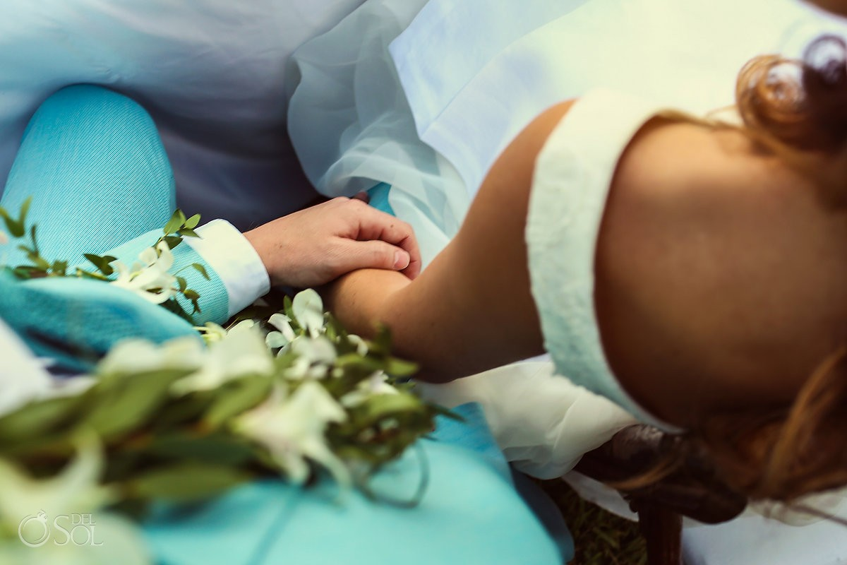groom in turquoise suit with Maile Lei from Hawaiian tradition holds hand with destination wedding bride