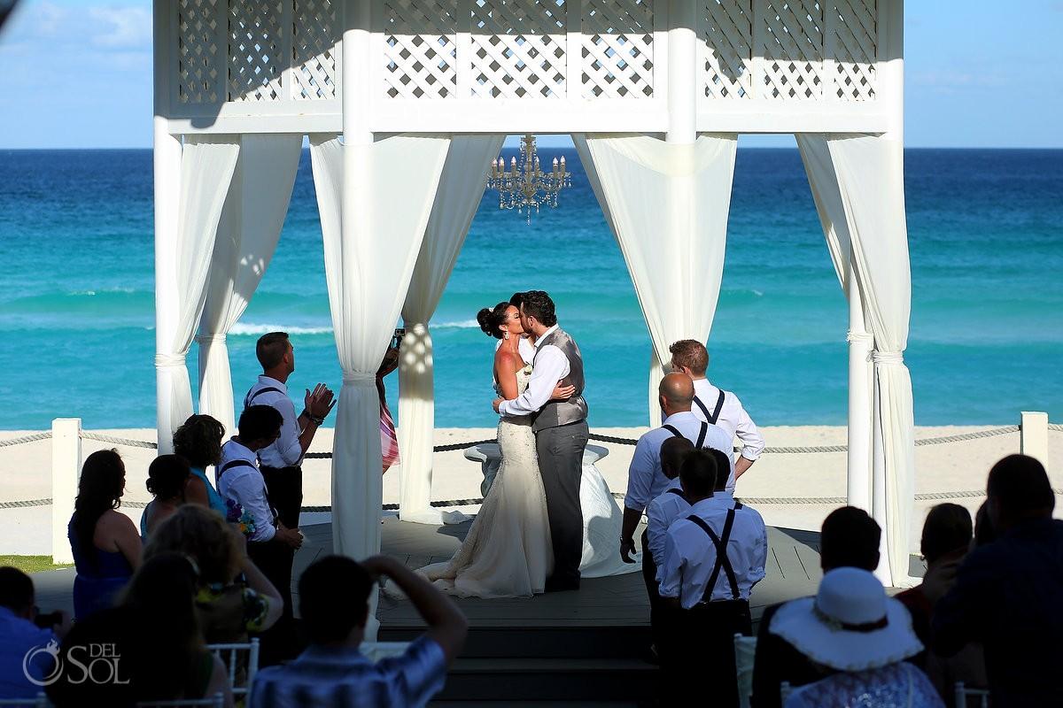 first kiss beautiful blue Caribbean ocean, Destination wedding ceremony Paradisus Cancun Gazebo, Mexico.
