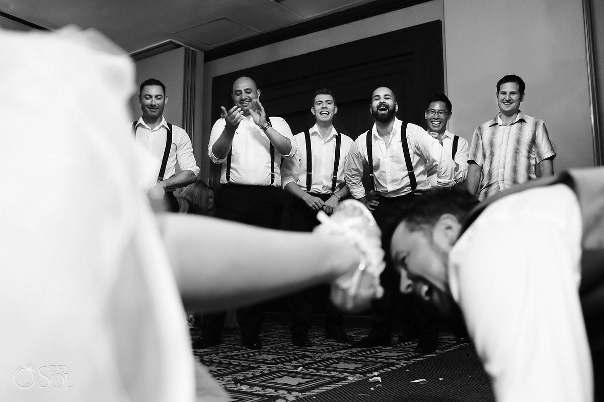 fun wedding picture groomsmen cheering garter toss black white Destination wedding reception Paradisus Cancun ballroom, Mexico.