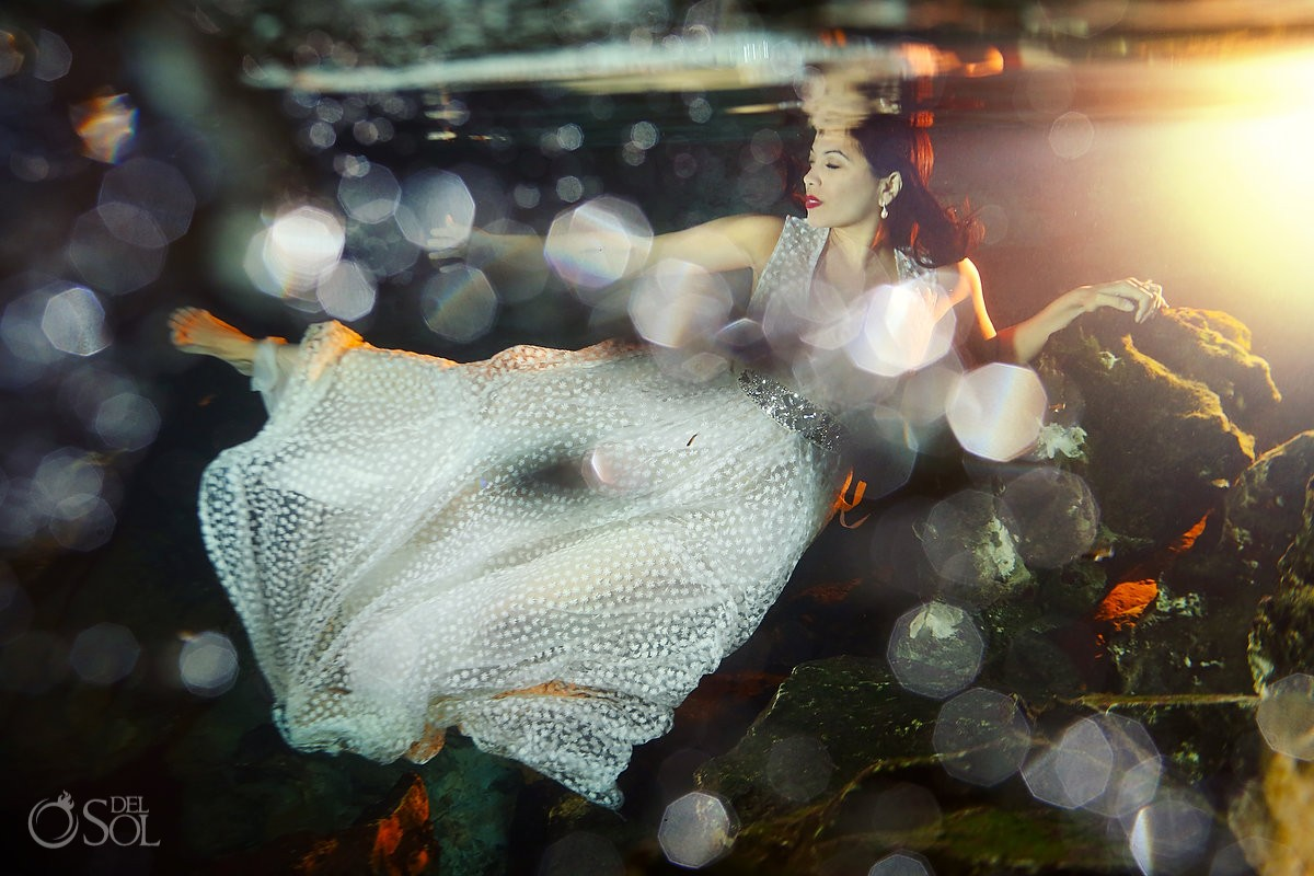 bride who can't swim featured in an underwater photo session Riviera Maya cenote trash dress