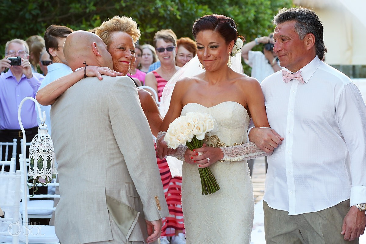 bride and groom hug parents at altar for destination wedding in mexico