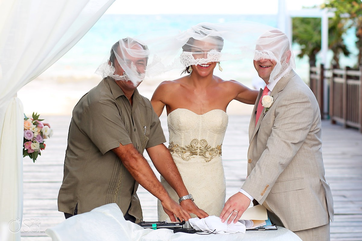 brides veil flys over officiant groom heads signing, funny wedding picture, Paradisus Gabi Bridge wedding