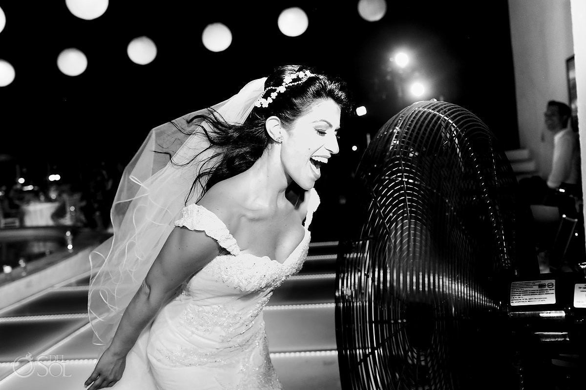 funny wedding photo bride cools off with big fan, destination wedding reception first dance Beach Palace Cancun Sky Terrace