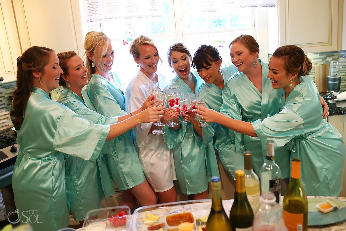 Bride and bridesmaids in green robes celebrate with a champagne toast