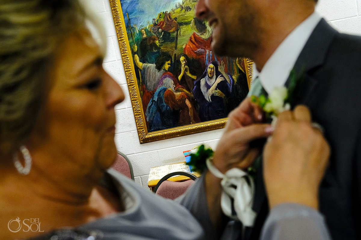 St. Simons wedding mother of the groom pinning boutonniere with a unique painting