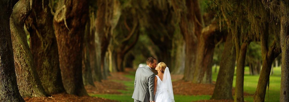 bride and groom kiss at avenue of the oaks st simons island wedding