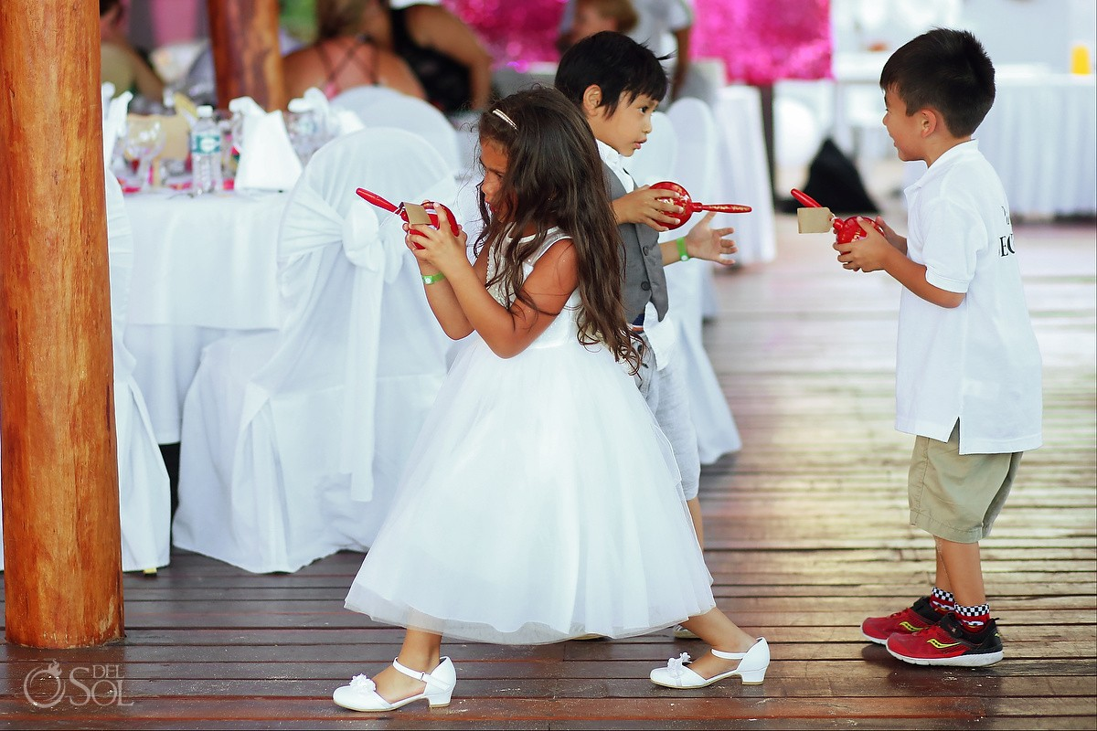 Flower girl cute kids playing with maracas, destination wedding reception, Grand Sunset Princess, Riviera Maya, Mexico.