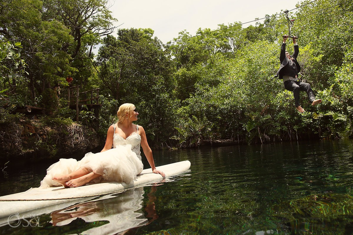 Fun wedding photo idea, trash the dress adventure groom riding zip-line over bride on paddle board