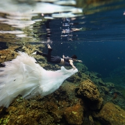 groom holding Eve of Milady Wedding dress underwater cenote photography Riviera Maya Mexico