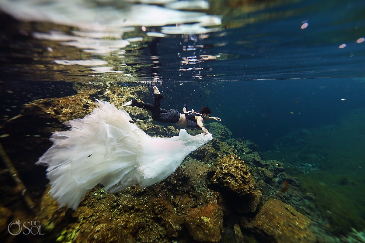 groom holding Eve of Milady Wedding dress underwater cenote photography Riviera Maya Mexico