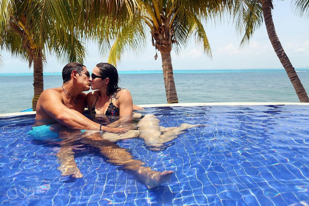 lovers in the pool with caribbean background Zoetry Villa Rolandi, Isla Mujeres, Cancun, Mexico.