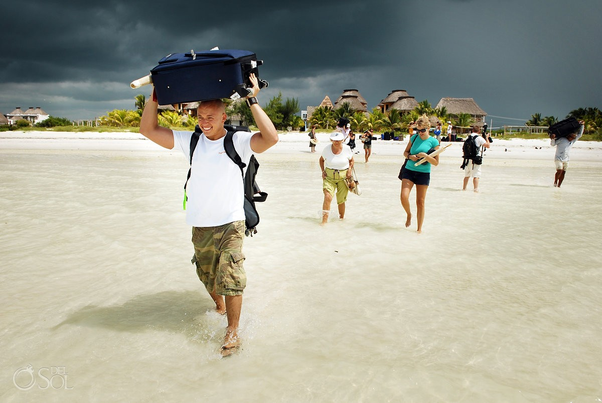 wedding guests carry bags as wedding is evacuated from holbox island hurricane dean