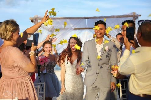 ceremony exit idea wedding guest throw bright yellow flowers confetti, just married, destination wedding Royalton Riviera Cancun, Mexico