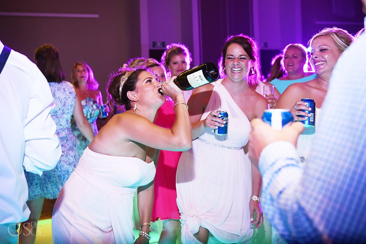Funny wedding reception pictures bridemaid swigging champagne from bottle Destination Wedding reception Secrets Silversands Riviera Cancun, Mexico