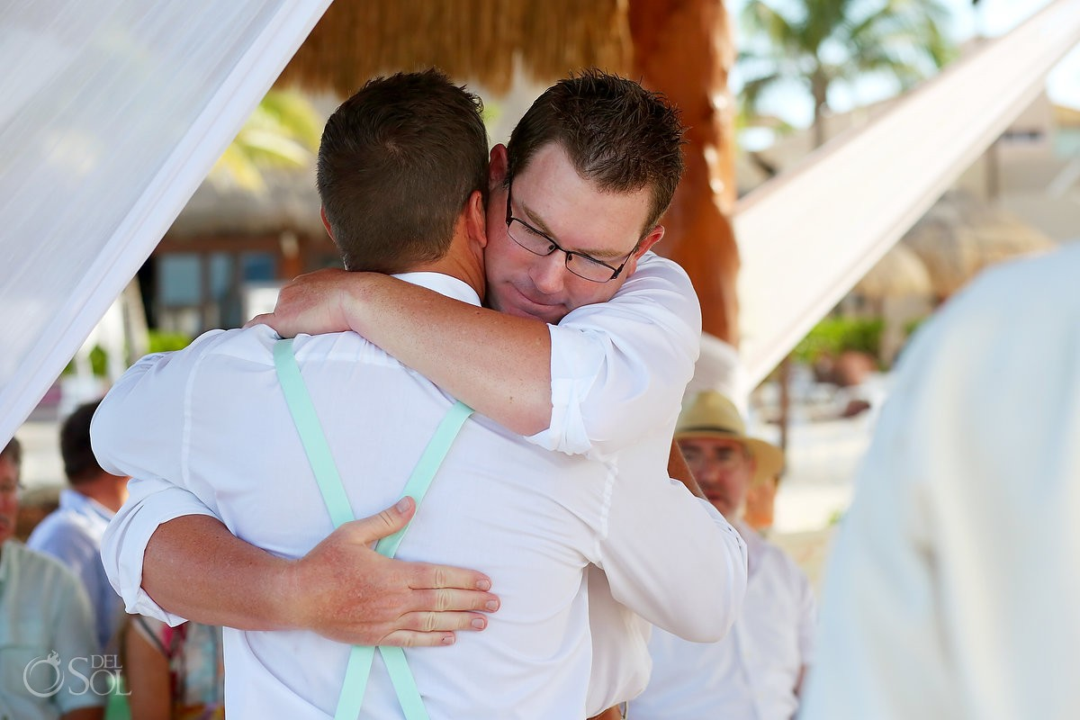 groomsman hugs groom processional Wedding at Dreams Puerto Aventuras, Riviera Maya, Mexico