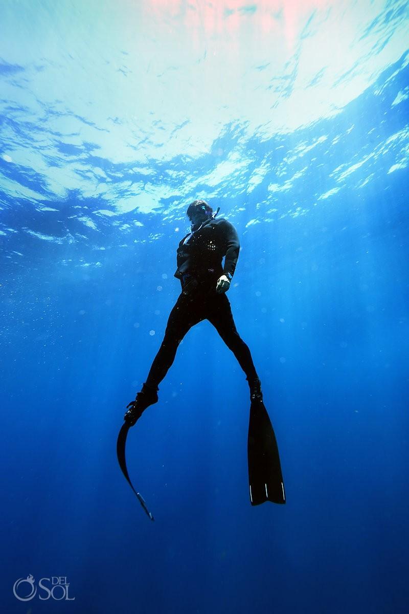 freediver swimming wearing true wet suit by Oceaner