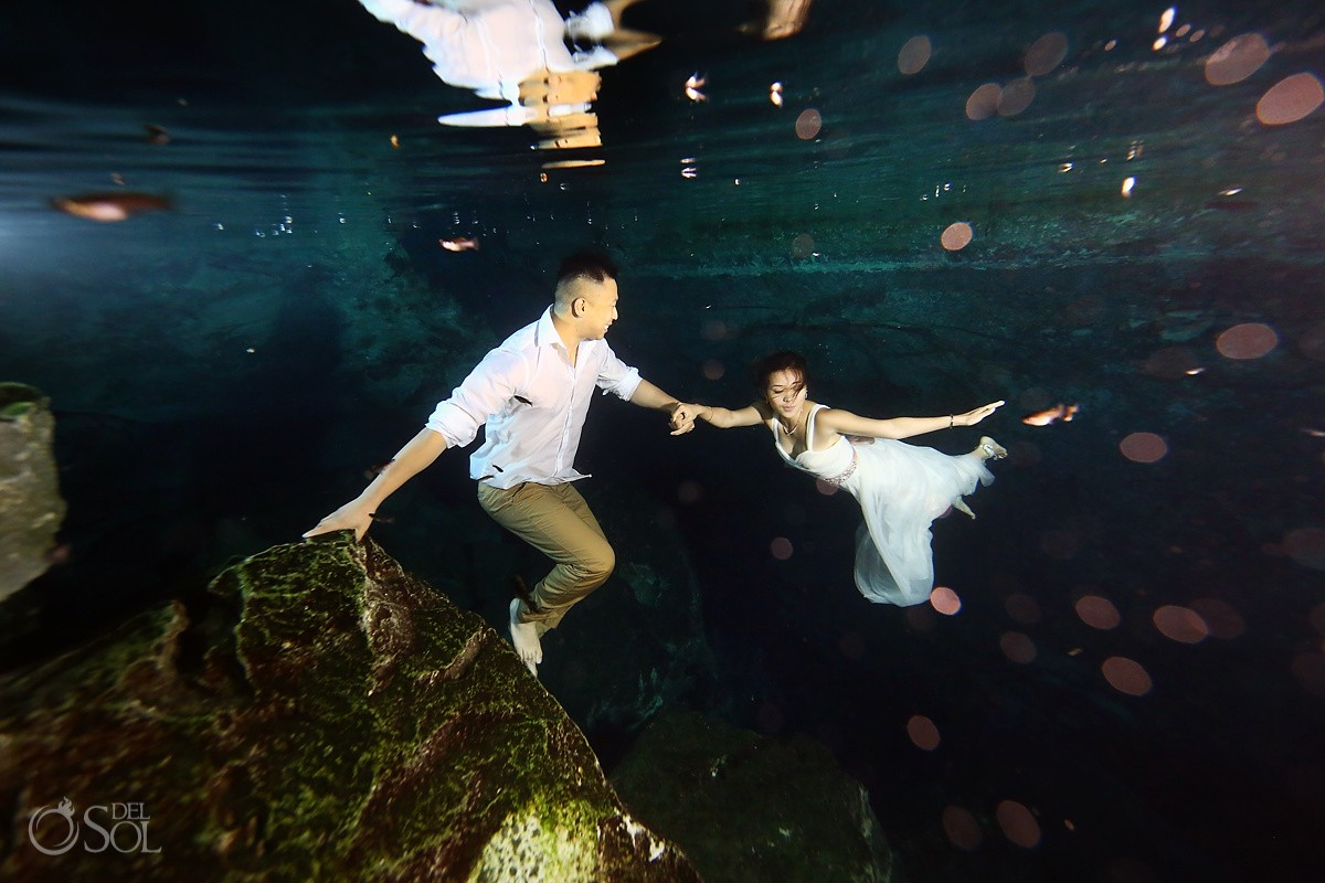 Underwater photograph bride groom cenote trash the dress Riviera Maya Mexico