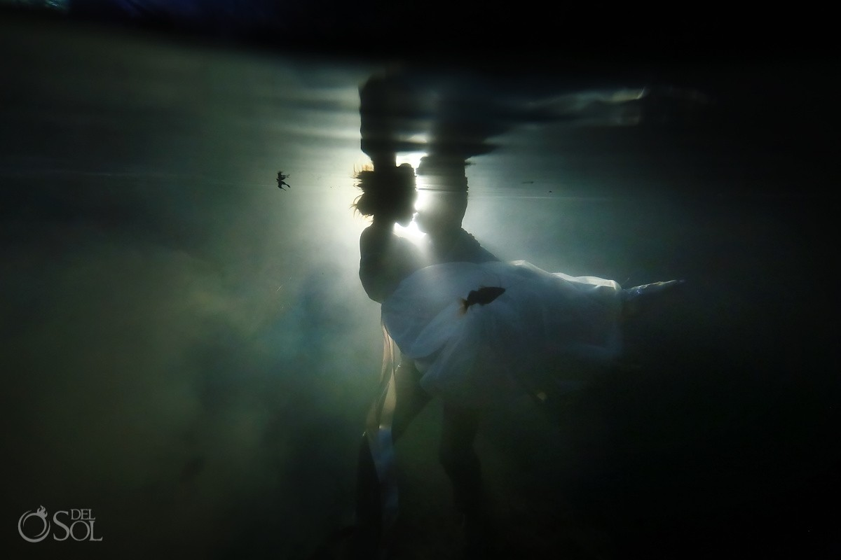 underwater photograph bride groom kissing