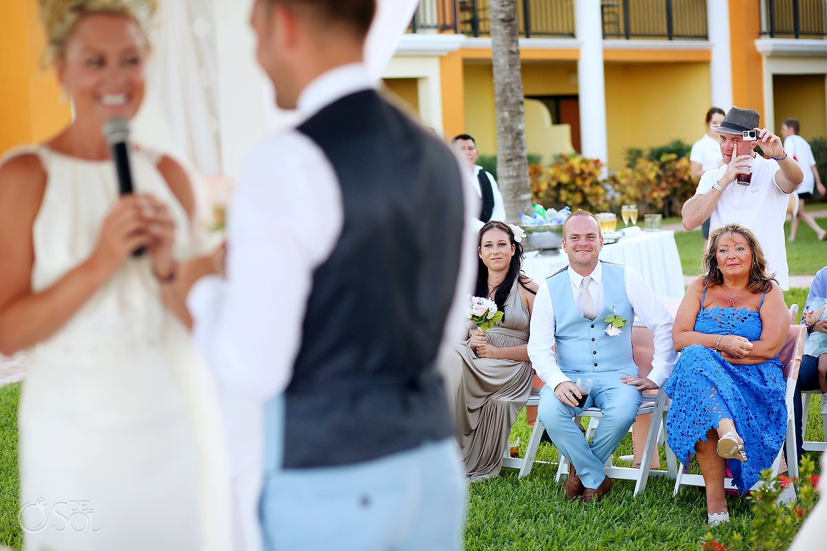 multitasking wedding guest crying filming with goPro and holding drink destination wedding Ocean Coral & Turquesa Gazebo