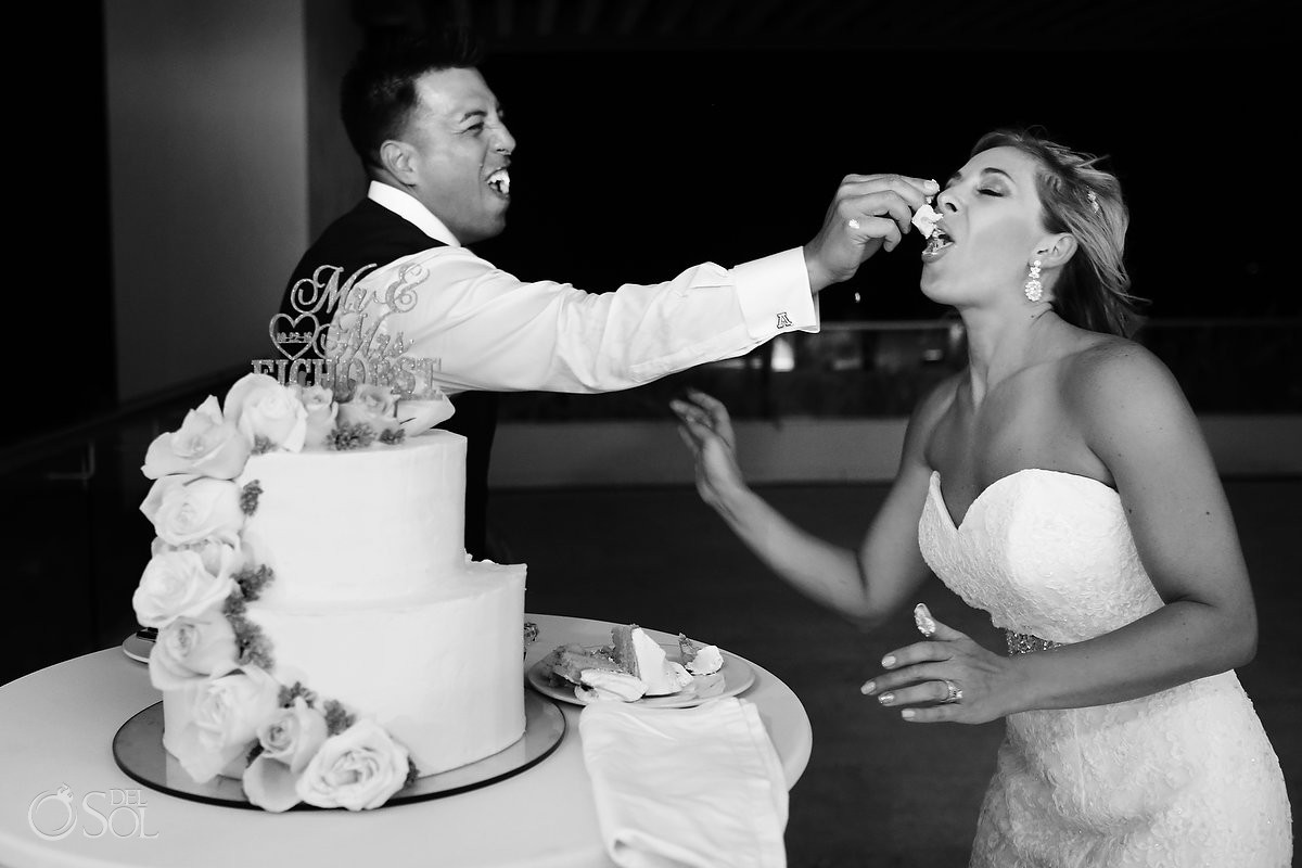 funny wedding picture cake cutting groom smashes cake on bride Destination wedding reception Hyatt Ziva Cancun Sky Terrace