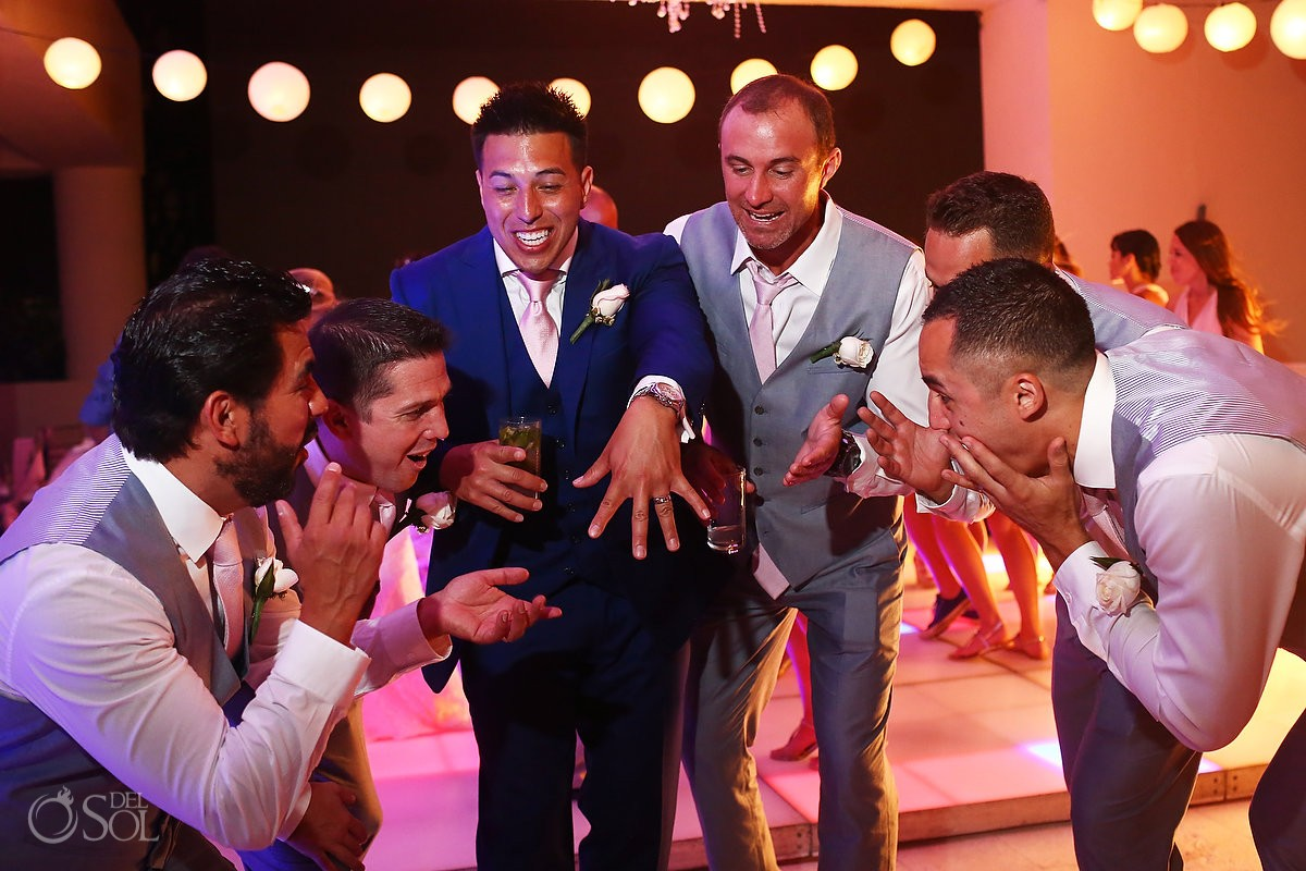 funny wedding picture idea groom shows off wedding ring to groomsmen Destination wedding reception Hyatt Ziva Cancun Sky Terrace