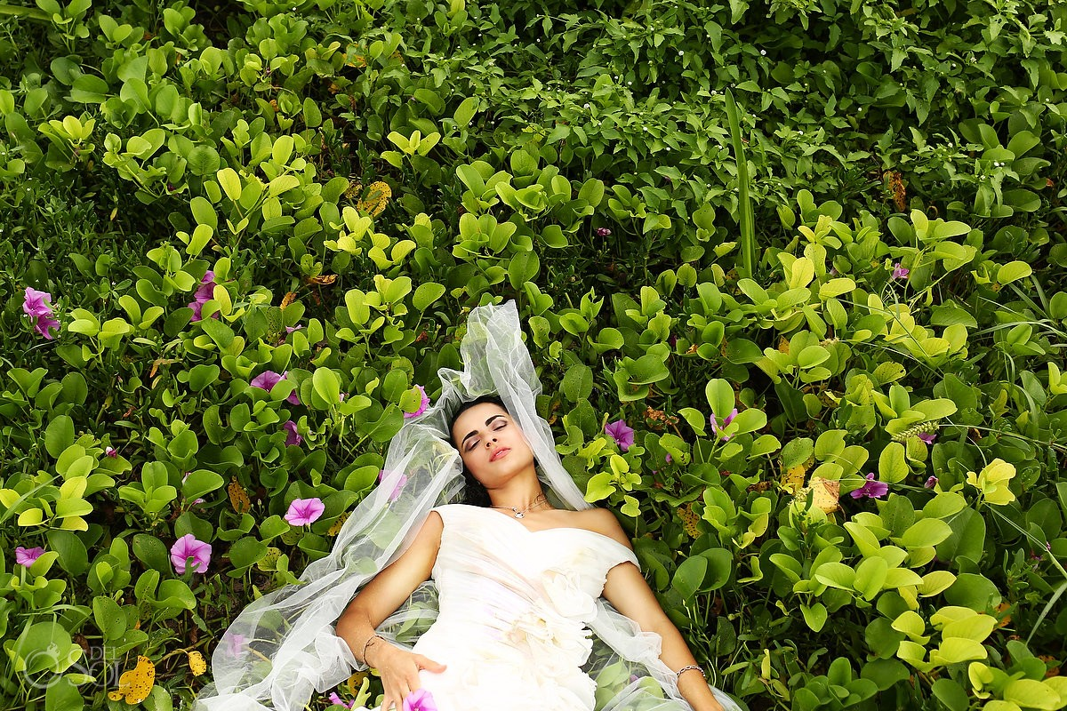 Beautiful bride lying in purple flowers, bride and baby unique beach trash the dress Playa del Carmen Mexico