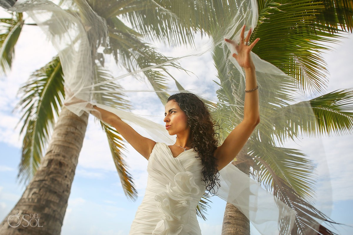 glamorous bride holding wedding veil palm trees beach trash the dress Playa del Carmen Mexico