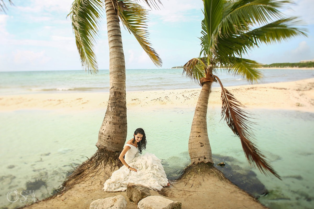 bride sitting under palm trees, fresh water lagoon in front of the Caribbean Ocean