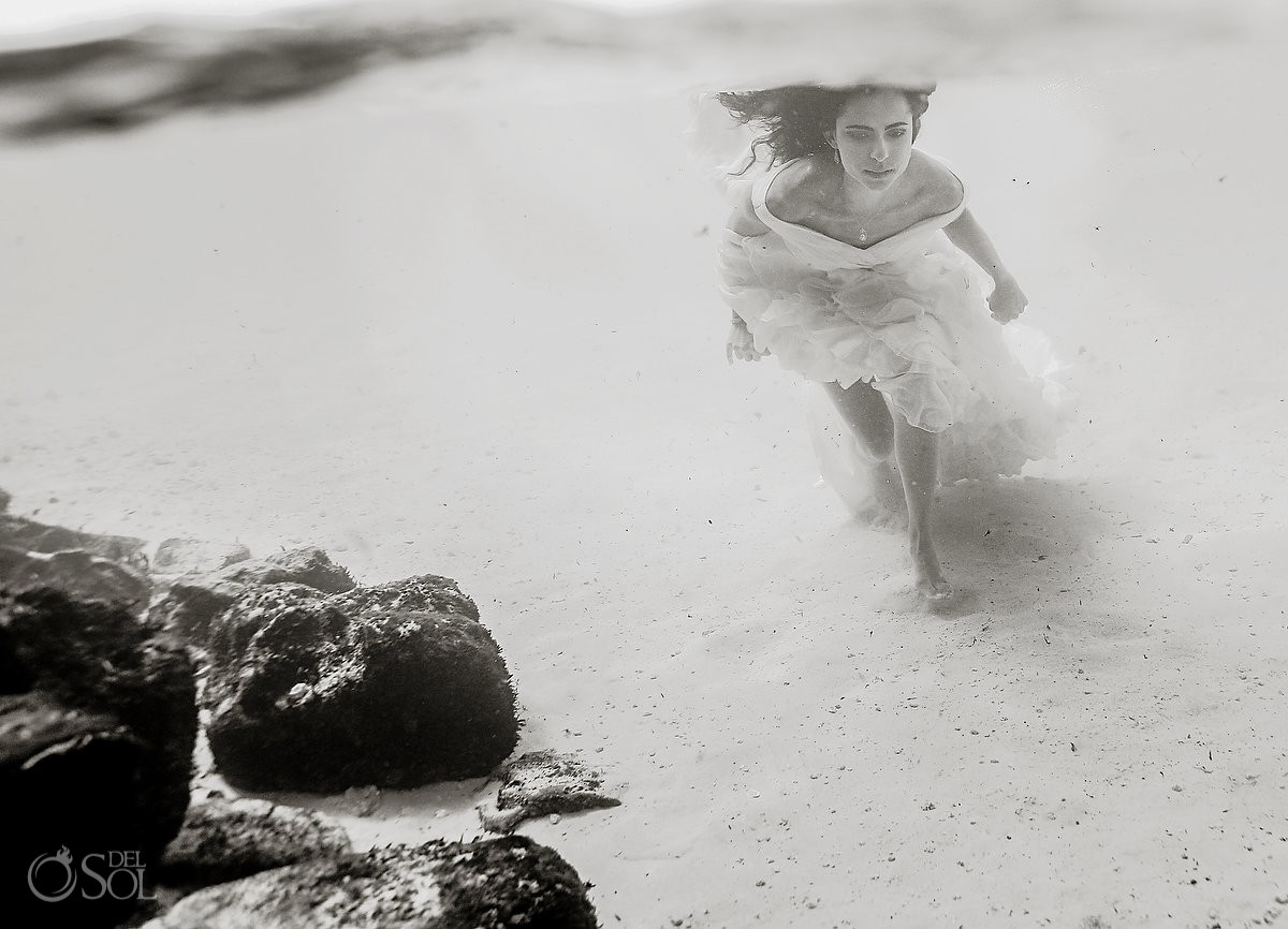 high key black and white beach underwater photograph bride running underwater