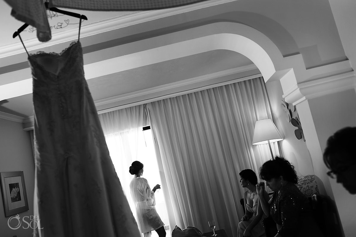 bride looking out of window with wedding dress hanging in foreground black white wedding photography getting ready Now Sapphire Resort Mexico