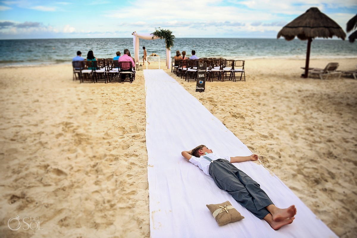 funny wedding photo ring bearer lying in middle of aisle destination wedding ceremony setup Now Sapphire beach