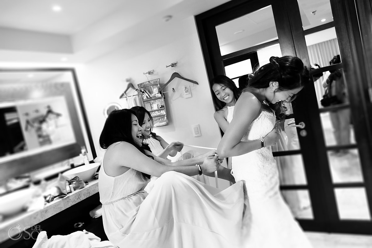 bridesmaids helping bride putting wedding dress getting ready Paradisus Playa del Carmen Mexico