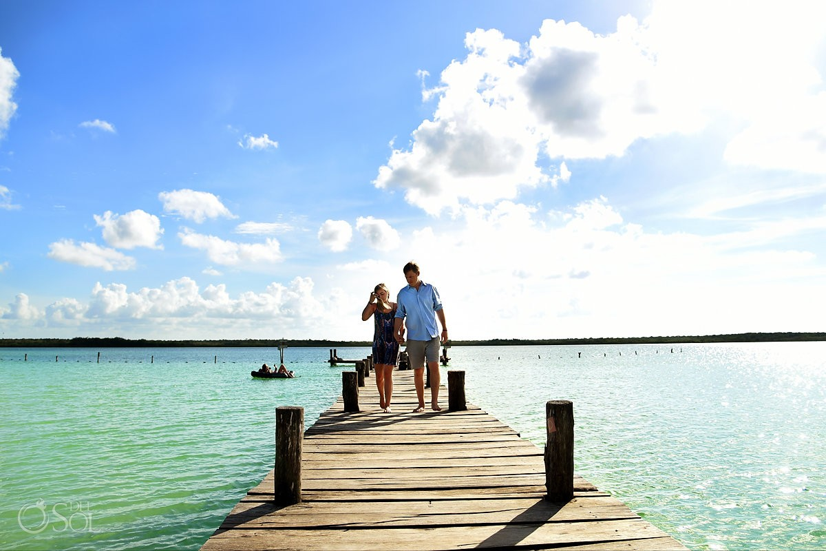Tulum Engagement Portraits couple walking along rustic wooden dock of Maya Kaan lagoon