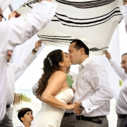 first kiss under Tallit prayer shawl Playa del Carmen Jewish Wedding Paradisus Riviera Maya Gabi Bridge