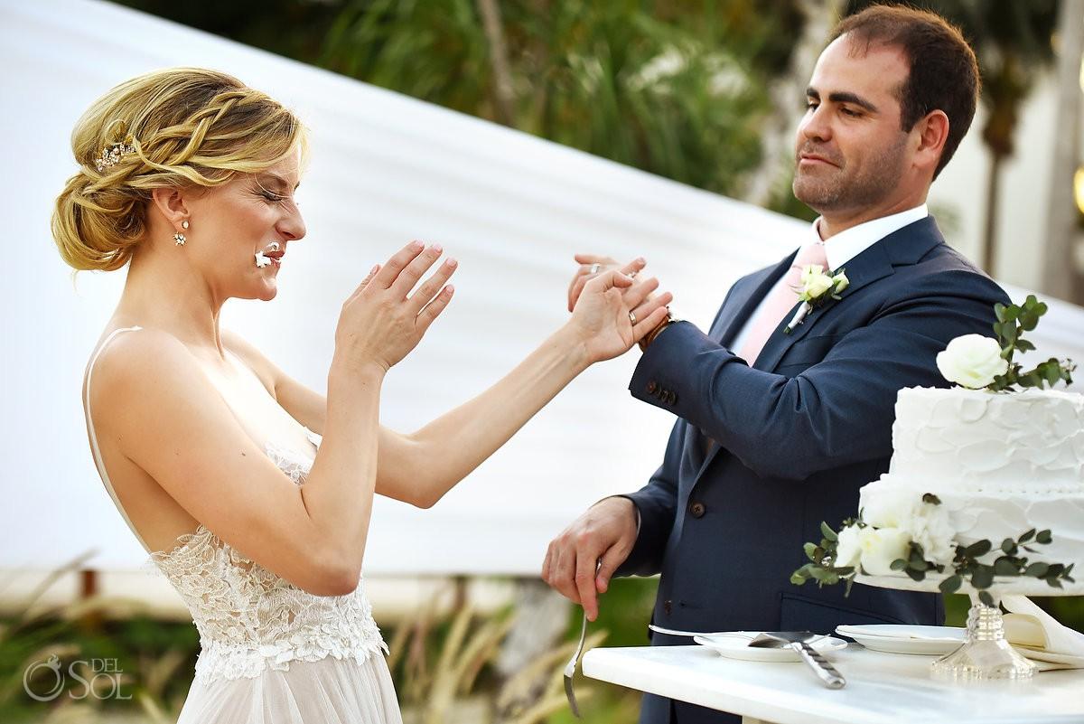 bride and groom smashing cake just married Secrets Akumal Riviera Maya Mexico