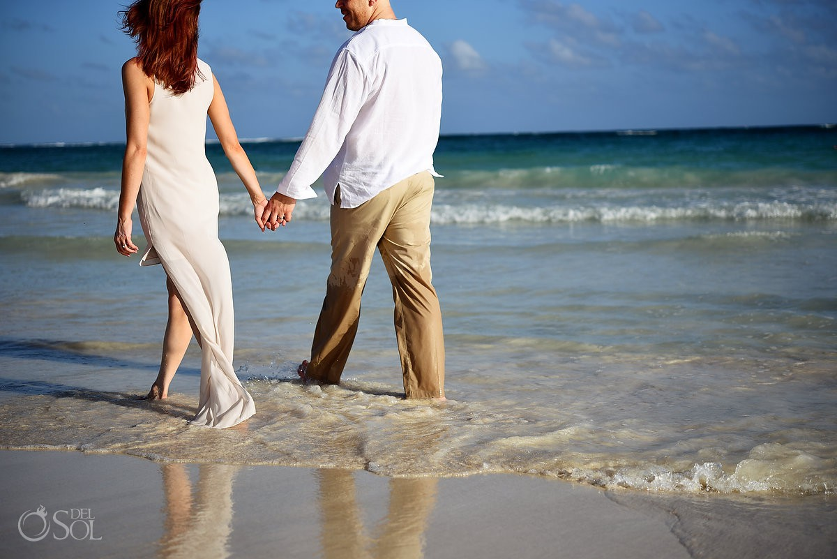 Romantic honeymoon portraits couple holding hands walking on the beach Dreams Tulum beach Riviera Maya Mexico